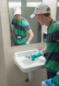 Spencer Lowe cleans a bathroom in the Jesse Knight Building Wednesday morning.